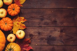 Thanksgiving background: Apples, pumpkins and fallen leaves on wooden background. Copy space for text. Halloween, Thanksgiving day or seasonal autumnal. Design mock up. Horizontal