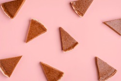 Thanksgiving bakery goods background with pumpkin pie slices random on a pink paper background. Flat lay of pie pieces pattern. Autumn cake pattern.
