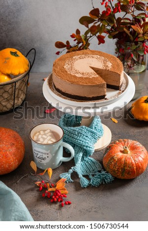 Thanksgiving concept. Chocolate mousse cake on stand with knitted scarf around it surrounded by autumn leaves and pumpkins, mug of hot cocoa on a gray table. Greeting card, cafe, confectionery, bakery