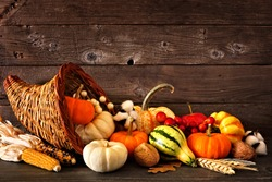 Thanksgiving cornucopia filled with autumn pumpkins and vegetables against a rustic dark wood background