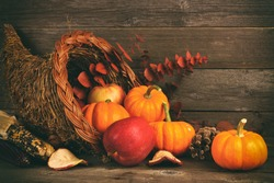 Thanksgiving cornucopia filled with pumpkins and apples against a rustic wooden background