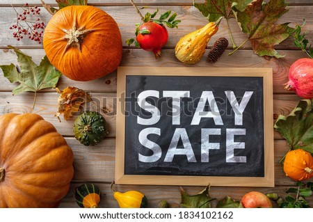 Thanksgiving COVID 19 days. STAY SAFE message  and thanksgiving flatlay on wooden background. Coronavirus protection