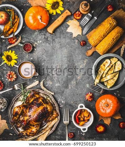 Thanksgiving dinner background with roasted turkey , sauce , pumpkin and dishes of  autumn vegetables on rustic background, top view, frame #699250123