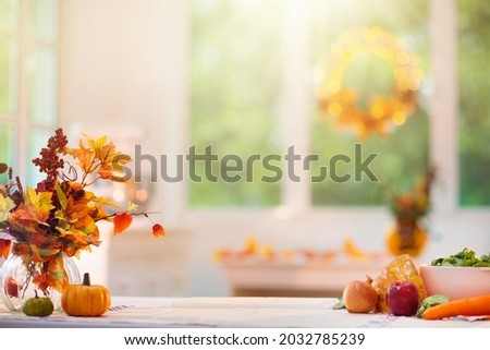 Thanksgiving dinner preparation. Table with pumpkin, carrot and onion for autumn season pie. Decorated kitchen in Halloween season. Cooking celebration feast. Fall seasonal vegetables.