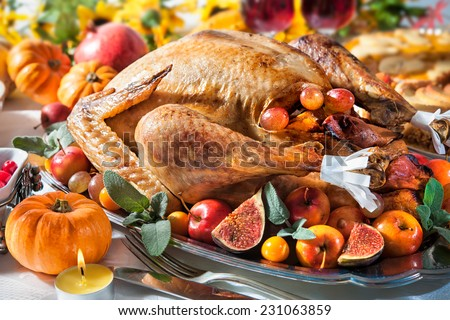 Thanksgiving dinner Roasted turkey on holiday table with pumpkins flowers and wine
