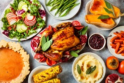 Thanksgiving dinner table with roasted whole chicken or turkey, green beans, mashed potatoes, cranberry sauce and grilled autumn vegetables. Top view, overhead.