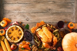 Thanksgiving dinner with chicken, cranberry sauce, pumpkin pie, wine, seasonal vegetables and fruits on wooden table, copy space. Traditional autumn holiday food concept.