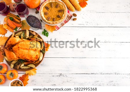 Thanksgiving dinner with chicken, cranberry sauce, pumpkin pie, wine, seasonal vegetables and fruits on white wooden table, copy space. Traditional autumn holiday food concept.