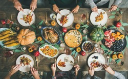 Thanksgiving, Friendsgiving holiday celebration. Flat-lay of friends eating meals at Thanksgiving Day table with turkey, pumpkin pie, roasted vegetables, fruit, rose wine, top view