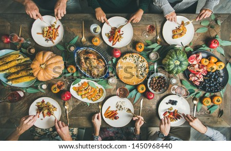 Thanksgiving, Friendsgiving holiday celebration. Flat-lay of friends eating meals at Thanksgiving Day table with turkey, pumpkin pie, roasted vegetables, fruit, rose wine, top view #1450968440