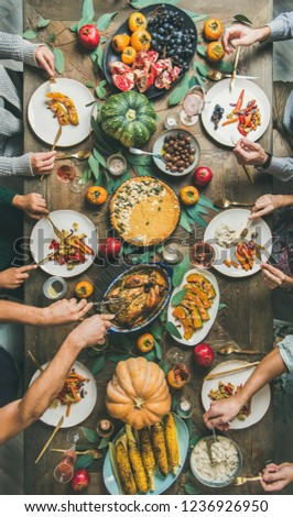 Thanksgiving, Friendsgiving holiday celebration. Flat-lay of friends feasting at Thanksgiving Day table with turkey, pumpkin pie, roasted vegetables, fruit, rose wine, top view, vertical composition #1236926950