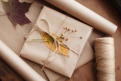 Thanksgiving gift wrapping. Autumn mood. Dry leaves herbarium nature kraft paper as decoration. Present birthday anniversary october