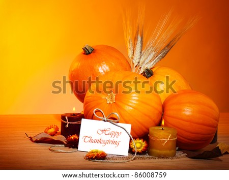 Thanksgiving holiday, pumpkin still life decoration with candles and wheat over yellow studio light background, greeting card with text space, harvest concept