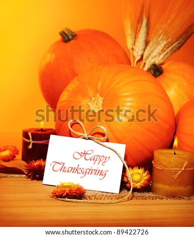 Thanksgiving holiday, pumpkin still life decoration with candles on the wooden table over yellow light background, greeting card with text space, harvest concept