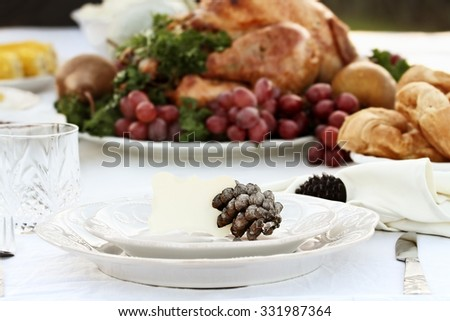 Thanksgiving Holiday table setting with croissants and roast turkey in background. Blank note card placed on plate. Extreme shallow depth of field with selective focus on card.