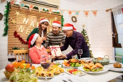 Thanksgiving or christmas Celebration Asian  Family Dinner Concept.Asian happy family celebrating Christmas with Grandparents while sitting over dining chair and wearing Santa Hat and with  gift box.