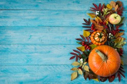 Thanksgiving or fall greeting background with border of apples, red berries, leaves and pumpkins on the rustic blue wooden table, copy space
