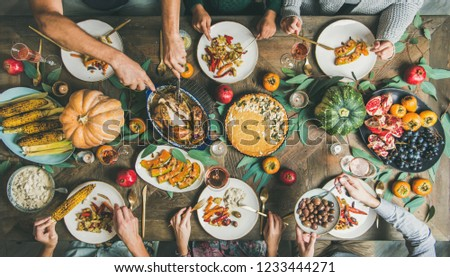 Thanksgiving or Friendsgiving holiday celebration party. Flat-lay of friends feasting at Thanksgiving Day table with turkey, pumpkin pie, roasted vegetables, fruit and rose wine, top view #1233444271