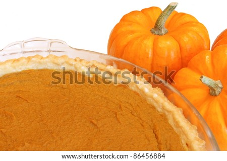 Thanksgiving pumpkin pie in a pie plate with pumpkins at side