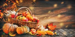 Thanksgiving pumpkins with fruits and falling leaves on rustic wooden table