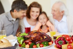 Thanksgiving roasted turkey on holiday table and family of four on background