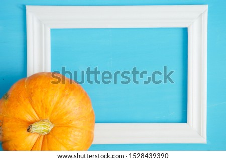 Thanksgiving season still life with orange pumpkins and with white frame for picture over rustic blue wood background Thanksgiving and Halloween concept. Copy space for text and design