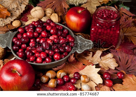Thanksgiving still-life with cranberries, autumn leaves, apples and nuts