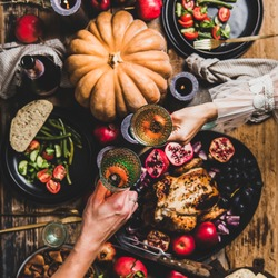 Thanksgiving table setting. Flat-lay of couple celebrating holiday with champagne at festive table with chicken, vegetables, fig pie, fruit, candles over wooden background, top view, square crop