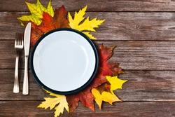 Thanksgiving table with an empty blue plate and orange leaves decoration on a wooden background. Autumn food background. Above view of an empty dish. Copy space, flat lay.