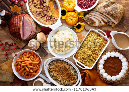 Thanksgiving table with roasted turkey, sliced ham and side dishes