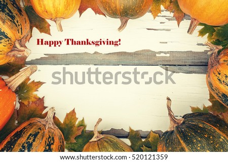 Thanksgiving. Toned image. Ripe pumpkin and autumn fallen leaves on a white vintage board. Decorated background, greeting card Thanksgiving Day. Happy Thanksgiving Day!