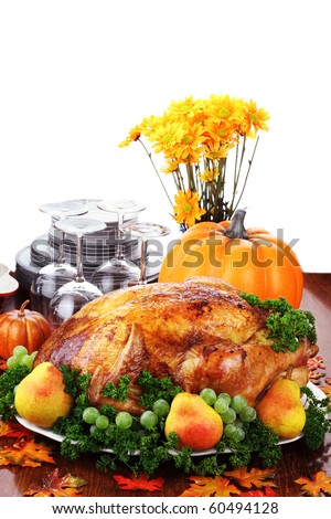 Thanksgiving turkey dinner with fresh fruit, dishes and flowers.