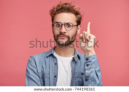 That is! Handsome clever student wonk or geek wears round glasses, raises finger as understands new theory, going to prove it, looks confidently, isolated over pink background. Confidence concept