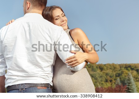 That is what love looks like. Horizontal portrait of a husband hugging his beautiful pregnant wife
