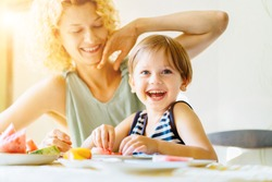 That's all, thanks. Woman play with her child. Family sit together at kitchen table. Mother refuses to eat, son try feeding her mother. mom and child are having lunch with watermelon fruits. Sun glare
