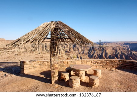 Thatch-roofed umbrella against canyon. Shot in Fish River Canyon National Park, Namibia.