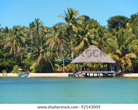 Thatched hut on tropical beach with houses hidden by coconut trees in background, Caribbean sea, Panama
