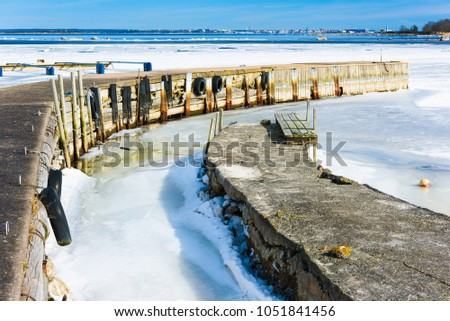 Thawing spring ice by a couple of jetties. Band of open sea in the distance. Meltwater close to the jetty. Location Hasslo island in southern Sweden. #1051841456