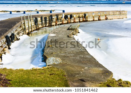 Thawing spring ice by a couple of jetties. Band of open sea in the distance. Meltwater close to the jetty. Location Hasslo island in southern Sweden. #1051841462