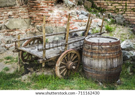 The abandoned cart and an old wooden barrel in the backyard.