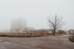 The abandoned factory building in the fog, the fence, the road