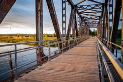The abandoned railway bridge over Jugla in Latvia. Old railway bridge converted into a pedestrian bridge. Sunset.