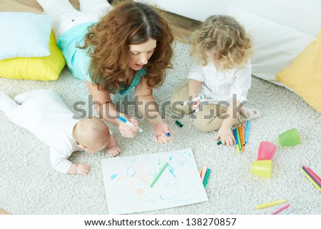 The above view of a happy family lying on the floor and drawing