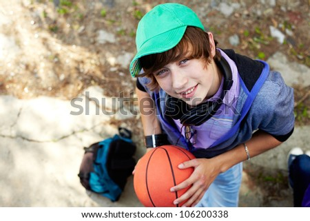 The above view of a smiling teen boy holding a basket-ball