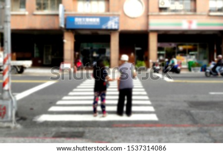 The abstract blurs the background of pedestrians crossing the sidewalk. The channels of the background and design elements are blurred. Defocused background with bokeh lights.