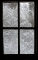 The abstract creation of window frost on window glass. Ornamental floral frost shapes on the window. Frost flowers. Poland, Europe