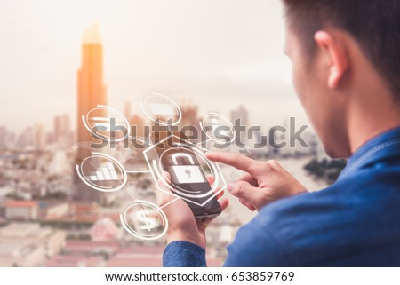 The abstract image of business man point to the hologram on his smartphone and blurred cityscape is backdrop. the concept of communication network cyber security internet of things and internet. #653859769