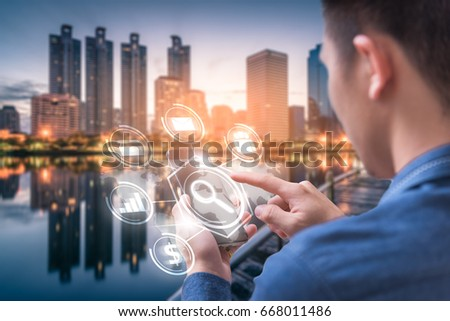 The abstract image of business man point to the hologram on his smartphone and blurred cityscape is backdrop. the concept of communication network cyber security internet of things and internet. #668011486