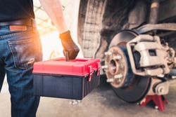 The abstract image of the back of technician hold a toolbox and blurred disc brake is backdrop. the concept of automotive, repairing, mechanical, vehicle and technology.