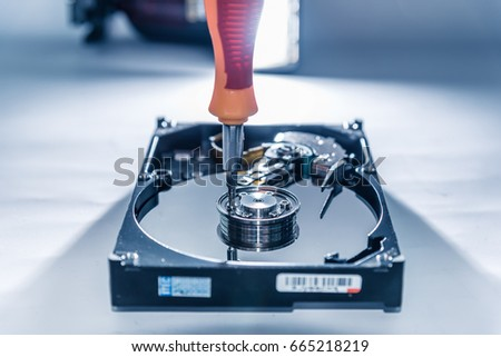The abstract image of the technician repairing inside of hard disk drive by screwdriver.  the concept of data, hardware, technician and technology.